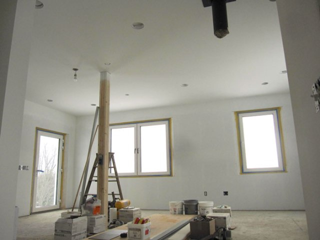 An ant's eye view of our kitchen-dining-living room.  New and improved with light fixtures, outlets, switches, sheetrock, and a first coat of paint!