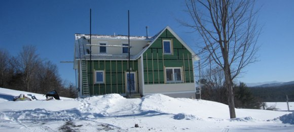 A snow covered view from the west - check out the start to our siding and window framing!